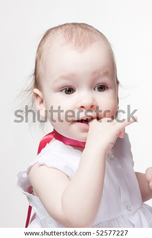 Studio portrait of cute baby holding finger at mouth