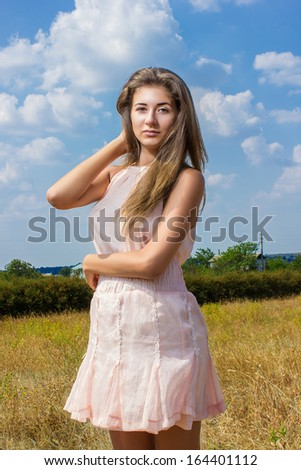 Studio portrait of cute girl on a background of the sky in a beautiful short dress
