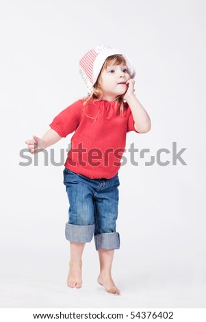 Studio portrait of cute interested child with finger at mouth