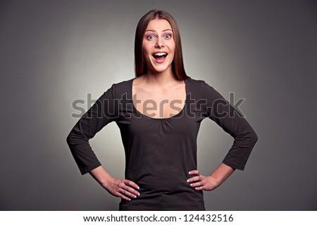 studio portrait of excited woman over dark background - stock photo