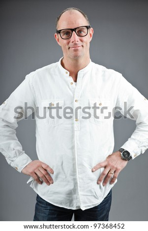 Studio portrait of expressive middle aged man wearing white shirt and retro glasses isolated on grey background - stock photo