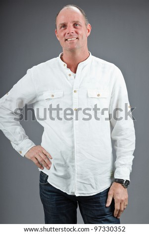 Studio portrait of expressive middle aged man wearing white shirt isolated on grey background - stock photo