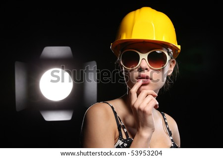 Studio portrait of fashionable female construction worker with bright spotlight over black background.