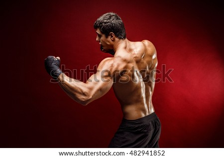 Studio portrait of handsome muscular fighter practicing boxing on red background