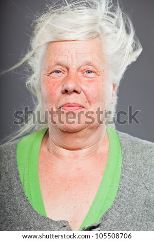 Studio portrait of happy senior woman with long hair in the wind. Studio shot isolated on grey background. - stock photo