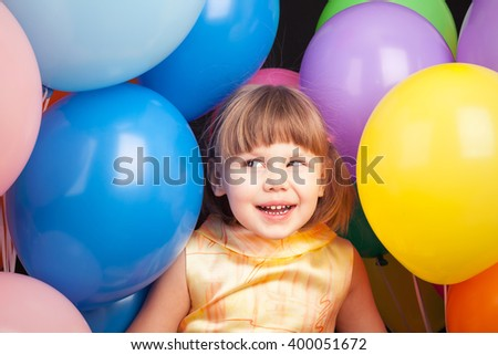 Studio portrait of laughing little Caucasian blond girl with colorful balloons