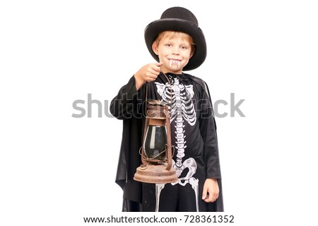 Studio portrait of little boy in Halloween costume against white background
