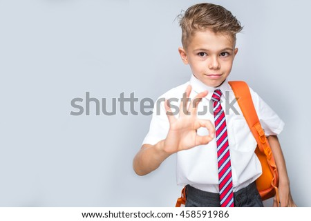 Studio portrait of male elementary pupil on light grey showing thumbs up, focus on face. back to school concept