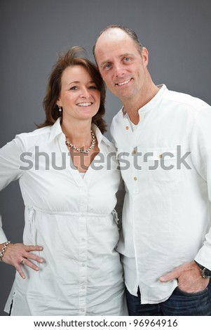 Studio portrait of middle aged couple wearing white shirt isolated on grey background