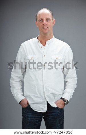Studio portrait of middle aged woman with white shirt isolated on grey background - stock photo