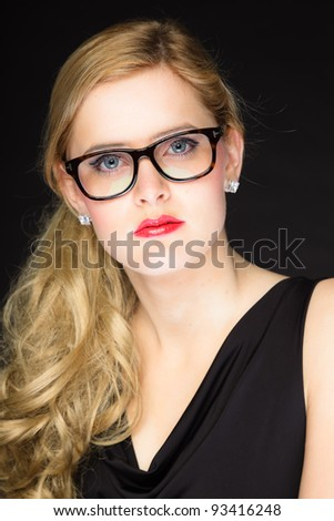 Studio portrait of pretty young woman with red lipstick and long blond hair wearing glasses. Wearing a black dress. Isolated on black background.