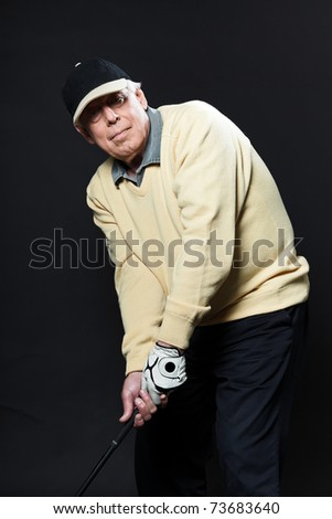 Studio portrait of senior golf man with yellow shirt and black cap preparing swing with golf club. Black background. Concentration. - stock photo