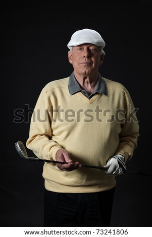 Studio portrait of senior golf man with yellow shirt and white cap. Black background. - stock photo
