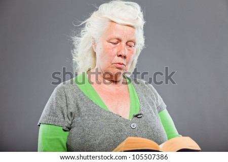 Studio portrait of senior woman reading a book. Studio shot isolated on grey background.