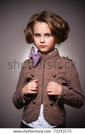 Studio portrait of serious stylish little girl looking at camera - stock photo