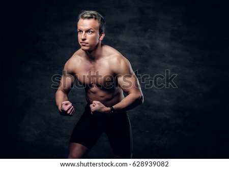 Studio portrait of shirtless athletic male with crossed arms over dark grey background.