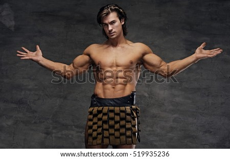 Studio portrait of shirtless athletic male with wide arms opened.
