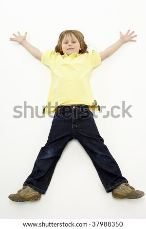 Studio Portrait of Smiling Boy lying down with arms and legs spread - stock photo