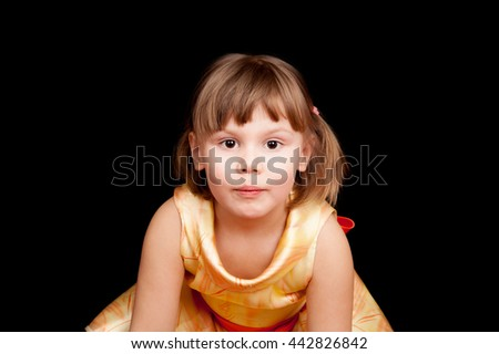 Studio portrait of smiling little Caucasian blond girl on black background - stock photo