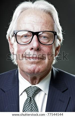 Studio portrait of smiling senior man in suit wearing glasses. - stock photo