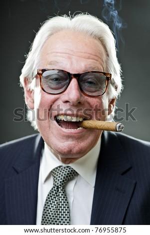 Studio portrait of smiling senior man in suit with big cigar wearing sunglasses. - stock photo