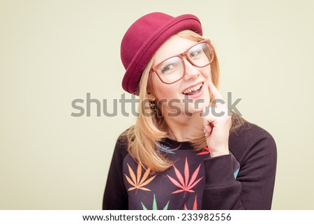 Studio portrait of teenage hipster girl wearing trendy eyeglasses and hat over olive copy space background - stock photo