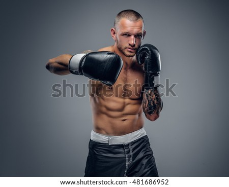 Studio portrait of the shirtless boxing fighter isolated on grey background.