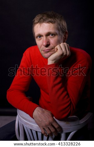 studio portrait of the thoughtful forty-year-old man on a black background - stock photo