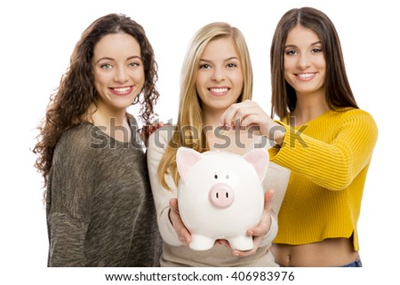 Studio portrait of three teenage girls holding a piggybank - stock photo
