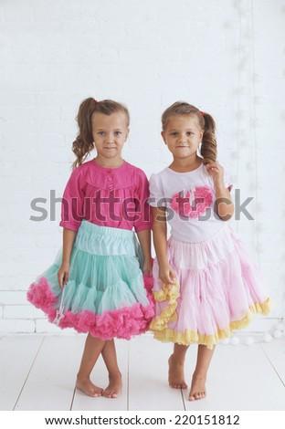 Studio portrait of two cute little princess girls wearing holiday candy tutu skirt holding magic wand - stock photo