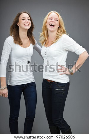 Studio portrait of two pretty young woman with white shirt isolated on grey background