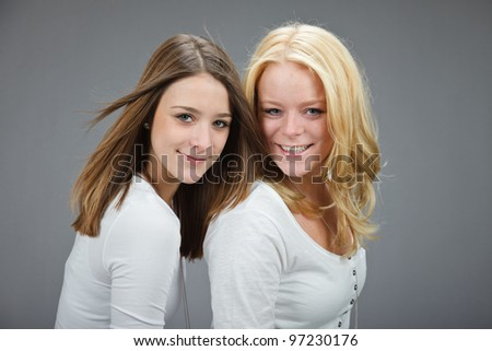 Studio portrait of two pretty young women with white shirt isolated on grey background
