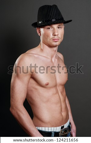 Studio portrait of young bald muscular man with black hat - stock photo