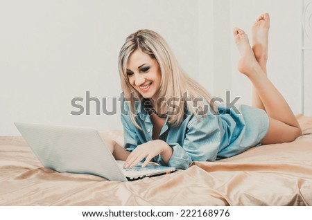 Studio portrait of young beautiful caucasian blonde woman with laptop on bed against white background. - stock photo