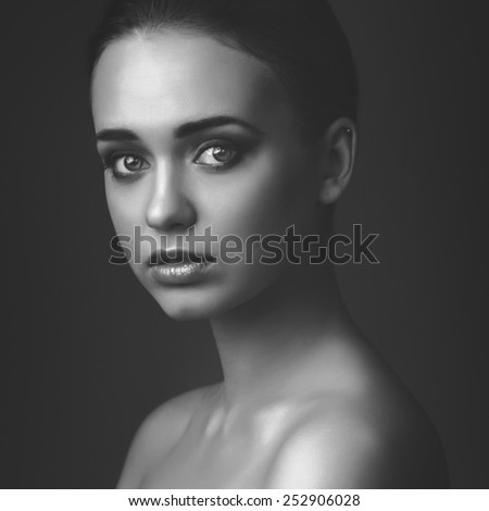 Studio portrait of young beautiful girl on dark background black and white