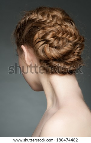 Studio portrait of young beautiful woman with blond hair and braid hairdo. Rear view - stock photo