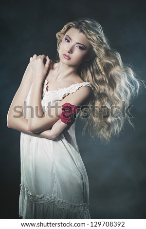 Studio portrait of young blond beautiful woman with roses in the smoke