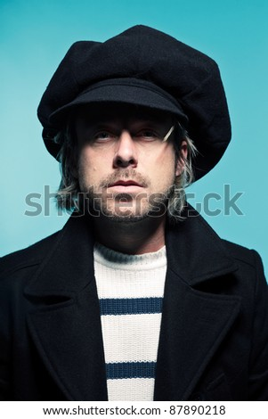 Studio portrait of young casual man with long blond hair wearing black hat and black jacket. Blue background.
