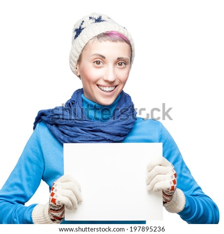 studio portrait of young cheerful blond caucasian girl in winter clothing which holding sign on white background - stock photo