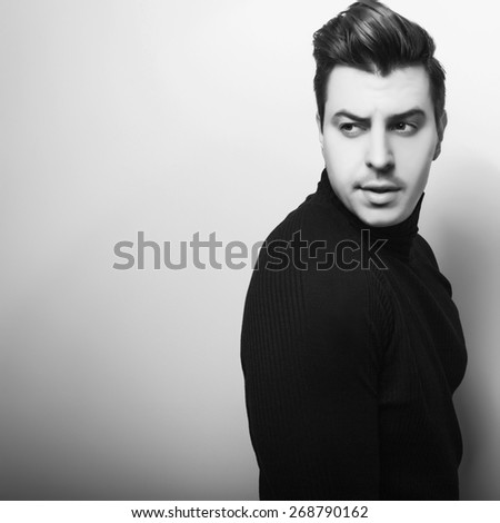 Studio portrait of young handsome man in black knitted sweater. Black-white close-up photo. - stock photo