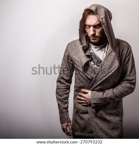 Studio portrait of young handsome man in casual cape with a hood. Close-up photo.  - stock photo