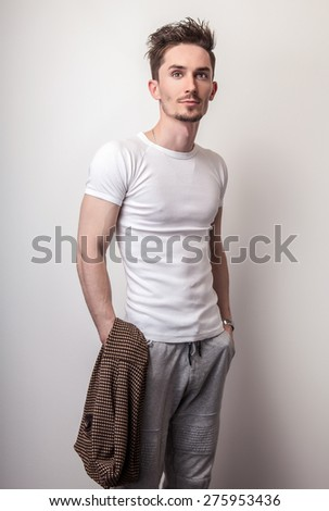 Studio portrait of young handsome man in casual white t-shirt.  - stock photo