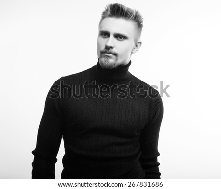Studio portrait of young handsome man in knitted sweater. Black-white photo. - stock photo