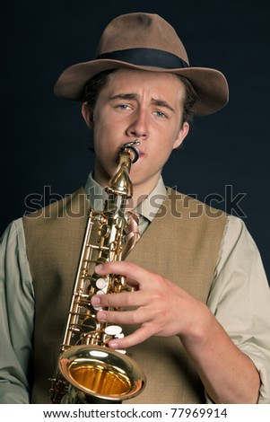 Studio portrait of young man in 20s style with saxophone wearing hat on black background.