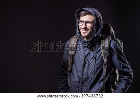 Studio portrait of  young man in winter jacket wearing backpack  - stock photo