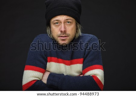 Studio portrait of young man long blond hair wearing woolen sweater and hat isolated on black background.