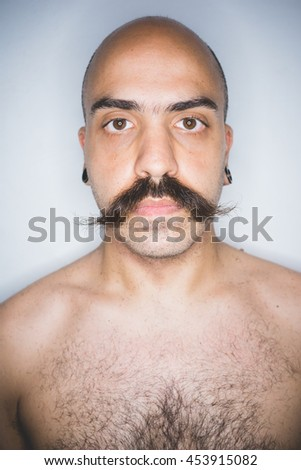 Studio portrait of young mid adult man with mustache looking at camera - beard care, wellness concept - stock photo