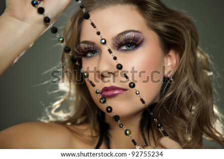 Studio portrait of young sensual woman looking at camera, professional make up and hair style