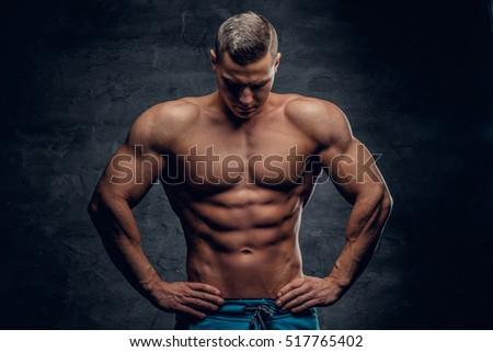 Studio portrait of young shirtless athletic male isolated with contrast illumination of grey vignette background.