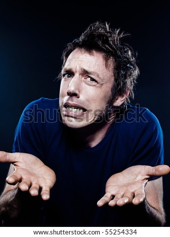 studio portrait on black background of a funny expressive caucasian man puckering interrogative hesitan - stock photo